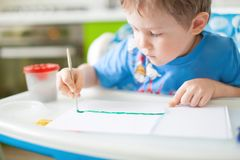 Happy cheerful child drawing with brush in album using a lot of painting tools. Creativity concept. Creativity concept. Happy cheerful child drawing with brush royalty free stock photo