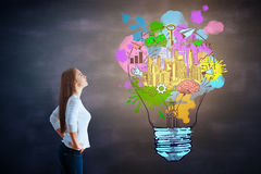 Creativity concept. Side view of attractive young european woman looking at chalkboard with business sketch. Creativity concept royalty free stock images
