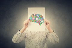 Creativity concept. Young Student,Businesswoman covering his face with a empty white paper with a colorulful brain made from gears over her head.Creativity Royalty Free Stock Image