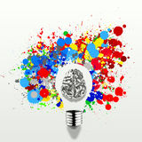 Creativity 3d metal human brain in visible light bulb. With splash colors background as concept Stock Photos