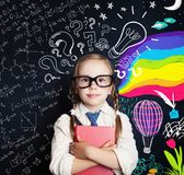 Creativity education, new ideas and right and left hemispheres. Of the brain concept. Smiling little girl on blackboard background with math and art pattern royalty free stock photography