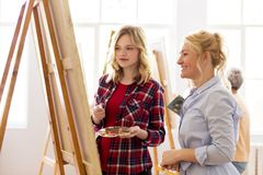 Artists discussing painting on easel at art school. Creativity, education and people concept - artists or student girl with palette and painting knife and Stock Photography