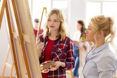 Artists discussing painting on easel at art school. Creativity, education and people concept - artists or student girl with palette and painting knife and Royalty Free Stock Image