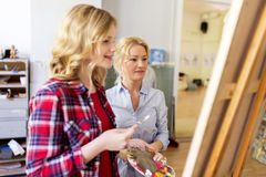 Artists discussing painting on easel at art school Stock Image