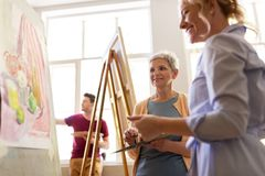 Artists discussing painting on easel at art school. Creativity, education and people concept - women artists discussing painting on easel at art school studio Stock Photography