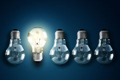 Creativity and innovation. Illuminated light bulb in a row of dim ones concept for creativity, innovation and solution royalty free stock photo