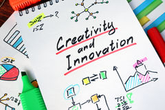 Creativity and Innovation. Notepad with Creativity and Innovation on a wooden surface Stock Photo