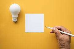 Creativity inspiration,ideas concept with lightbulb and notepad. Creativity inspiration,ideas concepts with lightbulb and notepad on pastel color background.Flat royalty free stock photography