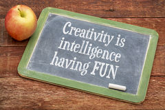 Creativity is intelligence having fun. Inspirational words  on a slate blackboard against red barn wood Stock Photography