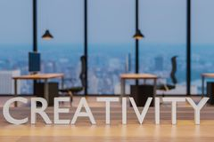 Creativity logo on clean wooden desk in modern office 3d rendering. Creativity logo on clean wooden desk in modern office with skyline view 3d rendering vector illustration