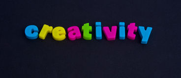 Creativity: possible logo. A macro image of the word creativity in colorful lower case letters isolated on a dark background royalty free stock photo