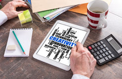 Creativity word cloud concept on a tablet. Man using a tablet showing a creativity word cloud concept royalty free stock photo