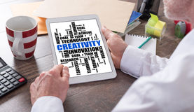 Creativity word cloud concept on a tablet. Creativity word cloud concept shown on a tablet held by a man stock photography