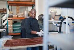 Creatore artigianale del cioccolato che lavora in una confetteria che fa fabbrica immagini stock