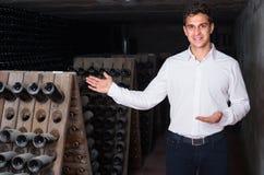 Creatore del vino in cantina con immagazzinamento nelle bottiglie di vino Fotografie Stock
