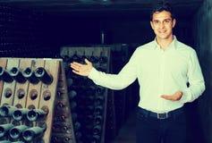 Creatore del vino in cantina con immagazzinamento nelle bottiglie di vino Fotografia Stock Libera da Diritti