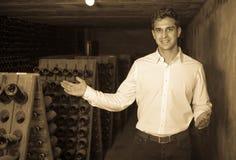 Creatore del vino in cantina con immagazzinamento nelle bottiglie di vino Fotografia Stock