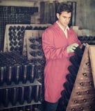 Creatore del vino che prende cura delle bottiglie del condimento Fotografia Stock