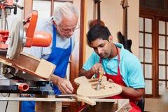 Creatore della chitarra ed apprendista del ` s di liutaio Immagini Stock Libere da Diritti