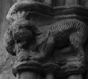Creature with face erased by time. Shot in black and white detail on the sculpture on the facade of this historic building representing some characters / animals royalty free stock image