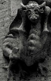 Creature with horns. Shot in black and white, detail on a capital with an sculpture  representing a strange creature placed on the facade of this historic Stock Image