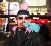 Creatures of the Night. An enterprising rodent trainer poses with his colorful companions, charging for photos, at New York's Times Square Stock Photo