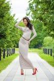 Crecimiento completo, mujer joven hermosa en vestido gris largo atractivo imagenes de archivo