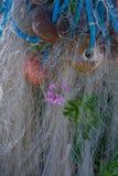 Crecimiento de flor rompiéndose a través de redes, de los flotadores y de infante de marina de pesca fotografía de archivo