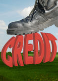 Credit and boot. A big fat credit about to be crunched by a workmans boot royalty free stock photography