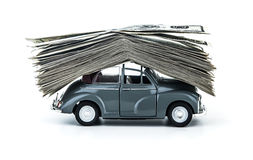 Credit for car. Side view on small decorative car model carries on itself a lot of cash isolated on white background, dollars of USA, credit for car concept Royalty Free Stock Images