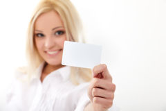 Credit card. Happy blond woman showing blank credit card. Focus on card