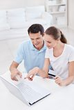 Credit card. A young couple with a credit card in the laptop looks stock photos