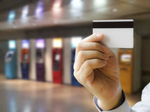 Credit Card. Hand show credit card with ATM machines as a backdrop Royalty Free Stock Photography