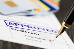 Credit card application approved, close up shot of a form, cards and pen. Royalty Free Stock Images