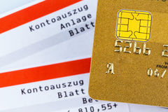 Credit card and bank statement. A golden credit card and bank statement .. symbolic photo for cashless purchases and status symbols Royalty Free Stock Photography