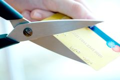 Credit card being cut by big pair of scissors Stock Images
