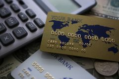 Credit card and calculator lying on big amount of US money royalty free stock images