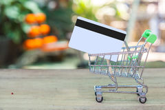 Credit card and cart or trolley. On wood Royalty Free Stock Photography