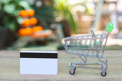 Credit card and cart or trolley. On wood Stock Image