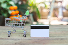 Credit card and cart or trolley. On wood Royalty Free Stock Photos