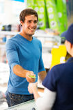 Credit card cashier. Happy young men handing over credit card to a female cashier at till point Royalty Free Stock Photo