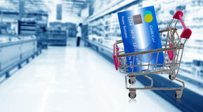 Credit Card Concept. Shopping trolley and  credit card on super market blur background, online payment, electronic commerce financial concept Royalty Free Stock Photos