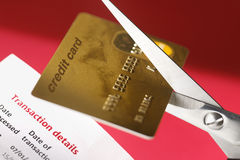 Credit Card Debt. Scissors cutting up credit card on red background Stock Image