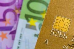 Credit card and euro banknotes. A gold credit card and euro banknotes. symbolic photo for cashless transactions and status symbols Royalty Free Stock Photos
