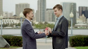 Credit card in exchange of money on a street of Coronado. Two young guys in suits are meeting on a sidewalk and one of them is giving away his money to another stock video footage