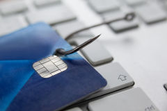 Credit card in fishing hook on laptop Stock Photo