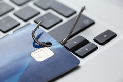 Credit card in fishing hook on laptop Royalty Free Stock Images