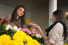Credit Card and Flower Shop, Happy service. Happy service by young women in flower shop Royalty Free Stock Photos