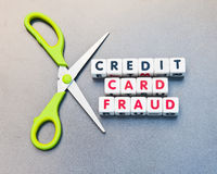 Credit card fraud. Scissors set against text ' credit card fraud ' inscribed in uppercase letters on small white cubes relating to theft of passwords and royalty free stock photography