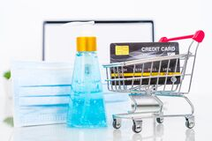 Credit Card Front Of Laptop Screen With Hand Sanitizer And Surgical Mask Stock Photos
